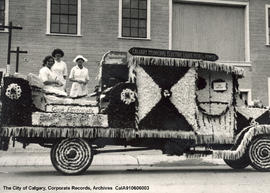 "Women posing on the ""Cooking Electrically"" float in the Stampede Parade, Calgary, Alberta."