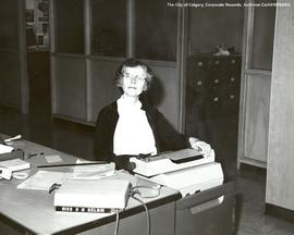 Gladys Belbin posing at her desk.