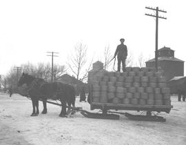 A ten ton load of wire being delivered to Chalmers' Hardware by L.G. Kelley's dray, Wet...