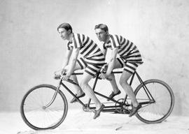 Frank Botterill and friend, dressed in striped short outfits, on a bicycle for two