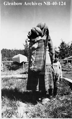 Ojibwa woman with children at Hudson's Bay Company (HBC) post, Long Lake, Ontario.