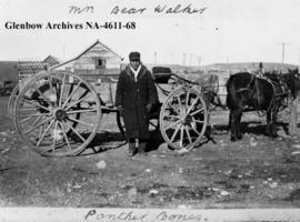 Panther Bone, a Blood man, standing in front of a wagon, southern Alberta.