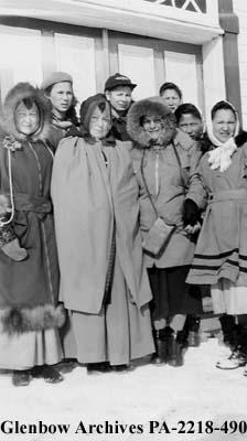 Sister A. Brady and group of children  outdoors in winter, probably Fort Chipewyan, Alberta.