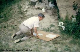 Selwyn Dewdney piecing together traced drawings of petroglyphs at Writing-on-Stone, Alberta.