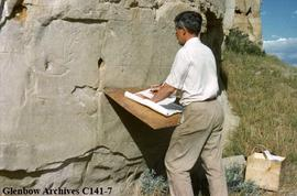 Selwyn Dewdney checking tracing with original petroglyphs at Writing-on-Stone, Alberta.