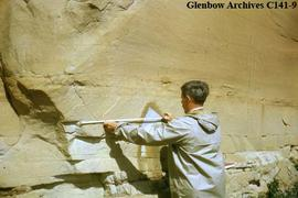 Selwyn Dewdney measuring petroglyphs and sketching to scale at Writing-on-Stone, Alberta.