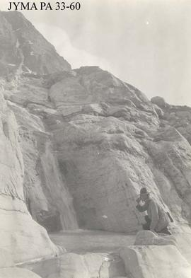 An unidentified man drinking from the source of the Smoky River at Robson Glacier, British Columbia.
