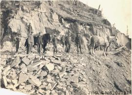 Group of men standing on a cliff with two horses.