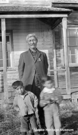 Man and two boys in front of Le Goff, Cold Lake school, Alberta