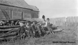 Boys on logs in front of Le Goff, Cold Lake church, Alberta