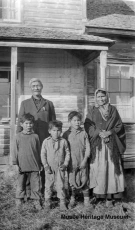 Man, woman and three boys in front of Le Goff, Cold Lake school, Alberta