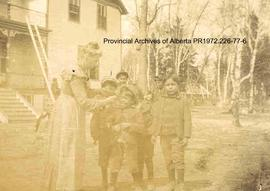 Presbyterian missionary and First Nations children in front of the Mission house at Shoal Lake, O...