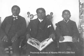 Portrait of three First Nations young men with books in the Lake of the Woods, Ontario area