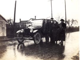 Four people standing beside a car, probably Prince Rupert, BC.