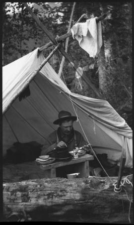 Man eating by tent