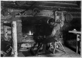 Elliott Barnes in front of fireplace at his Kootenay Plains cabin