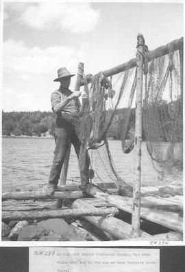 An old Nova Scotia fisherman mending his nets while they dry in the sun on Nova Scotia's Sou...