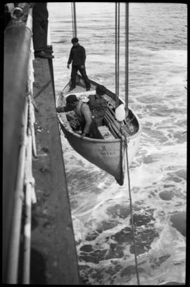 People being lowered in lifeboat